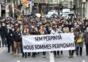 Demonstrators hold a banner reading 'We are Perpignan' as they stage a protest in Perpignan, south-western France on April 10, 2021, against the new logo of the city, a decision made by the extreme right-wing, 'Rassemblement National' (RN) Mayor. (Photo by RAYMOND ROIG / AFP)